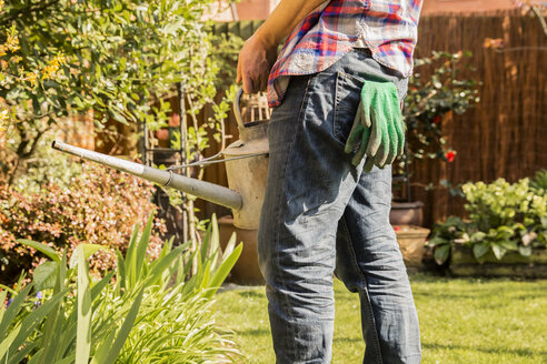 Close-up of man holding watering can in garden - NMS00315