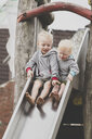 Two barefoot siblings together on a slide - IHF00057