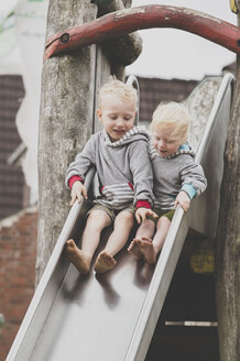 Two siblings, a boy and a girl, trying to slide down together, Sylt, DE - IHF00057