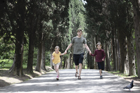 Father with two kids running on a treelined road - EYAF00249