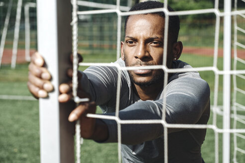 Portrait of sportsman stretching exercise behind net - AHSF00403