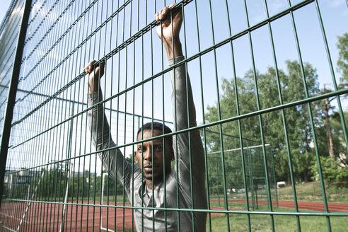 Portrait of sportsman behind fence - AHSF00421