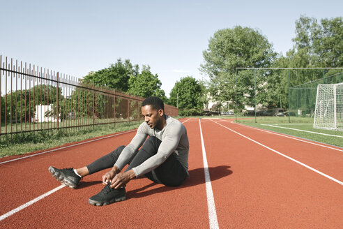 Sportsman sitting on racetrack and tying shoes before workout - AHSF00430
