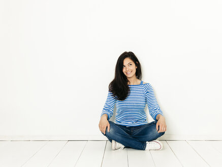 Beautiful young woman with black hair and blue white striped sweater sitting on the ground in front of white background - HMEF00416