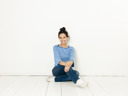 Beautiful young woman with black hair and blue white striped sweater sitting on the ground in front of white background - HMEF00419