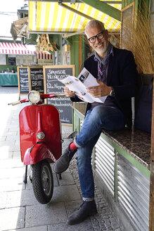 Mature man waiting at the market, reading brochure - ECPF00757