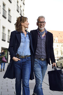 Mature couple walking in the city, with arms around - ECPF00763