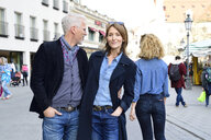 Mature couple walking in the city, man looking after an other woman - ECPF00769