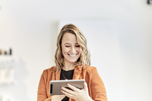 Portrait of smiling young businesswoman using mini tablet - FMKF05680