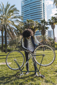 Casual businessman examining bicycle in urban park, Barcelona, Spain - AFVF03050
