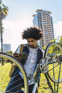 Casual businessman with cell phone and bicycle in urban park, Barcelona, Spain - AFVF03053