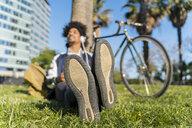 Casual businessman taking a break in urban park listening to music, Barcelona, Spain - AFVF03062