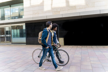 Two casual businessmen with bicycle walking in the city, Barcelona, Spain - AFVF03080