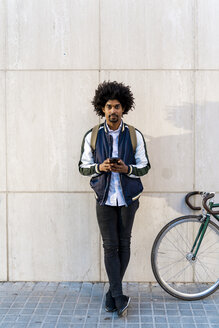 Portrait of casual businessman with bicycle and cell phone standing at a wall - AFVF03131