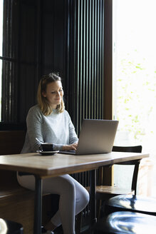 Smiling young woman using laptop in a coffee shop - FBAF00636
