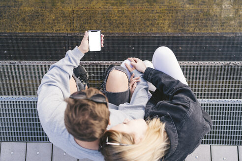 Young couple sitting stairs looking at smartphone - FBAF00651