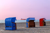 Three hooded beach chairs at sunset, Warnemuende, Rostock, Germany - PUF01601