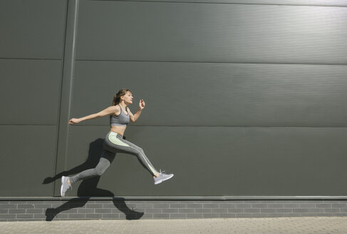 Sportswoman jumping in front of grey wall - AHSF00443