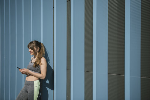 Sportswoman using phone in front of blue wall - AHSF00446
