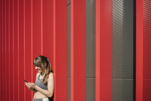 Sportswoman using phone in front of red wall - AHSF00449
