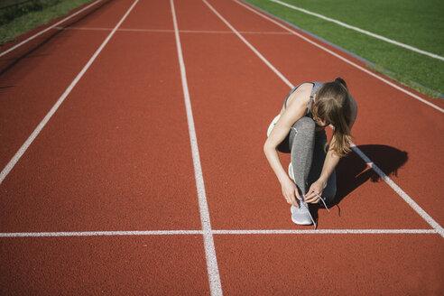 Sportswoman on racetrack tying shoes - AHSF00458