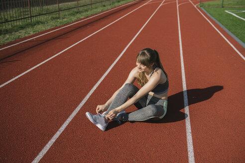Sportswoman on racetrack tying shoes - AHSF00464
