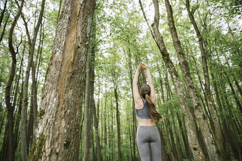 Rear view of woman stretching his arms in the forest - AHSF00491
