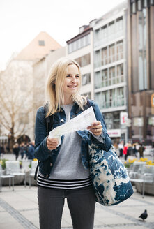 Portrait of smiling blond woman with map and baggage in the city, Munich, Germany - HMEF00429