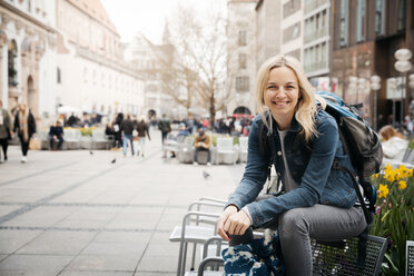 Portrait of smiling blond woman with baggage in the city, Munich, Germany - HMEF00432