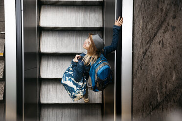 Woman with backpack and travelling bag standing on escalator looking up - HMEF00435