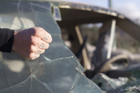 Fist of a young man with HOPE tattoo on broken windscreen on a scrapyard - JPTF00075