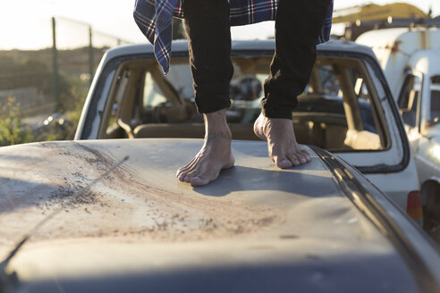 Young man walking barefoot on car roof on a scrapyard - JPTF00081