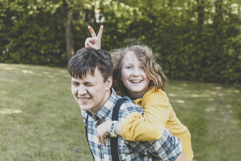 A smiling girl riding on her big brother's back - IHF00067