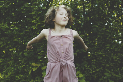 A girl jumping with eyes closed - IHF00070