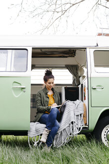 Young woman sitting in her camper, writing in a notebook - HMEF00437