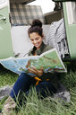 Young woman studying map, sitting in the grass, in front of her camper - HMEF00443