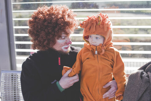 Man dressed up as a clown and little boy dressed up as lion baby at carnival - IHF00085