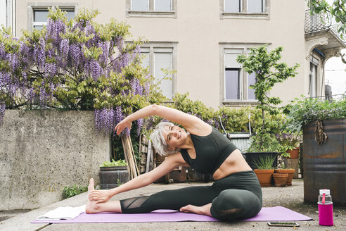 Woman practising yoga on a roof terrace - FBAF00661