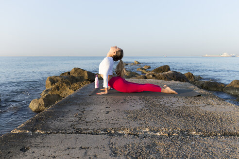 Young woman practicing yoga on the beach, doing cobra pose - JPTF00093