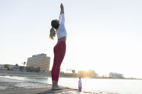 Young woman practicing yoga on the beach, doing sun salutations - JPTF00096