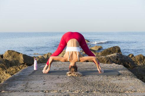 Young woman practicing yoga on the beach, doing prasarita padottanasana - JPTF00099