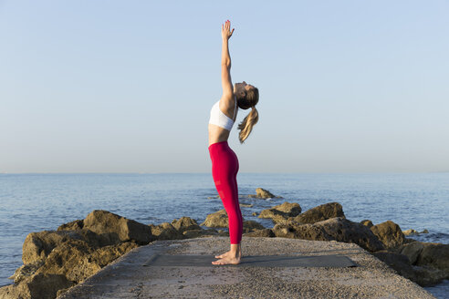 Young woman practicing yoga on the beach, doing sun salutations - JPTF00102