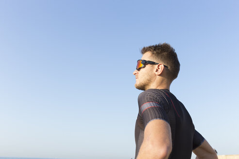 Triathlete standing in the sun against clear blue sky - JPTF00108