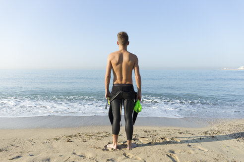Rear view of young athlete on the beach, preparing to swim - JPTF00111
