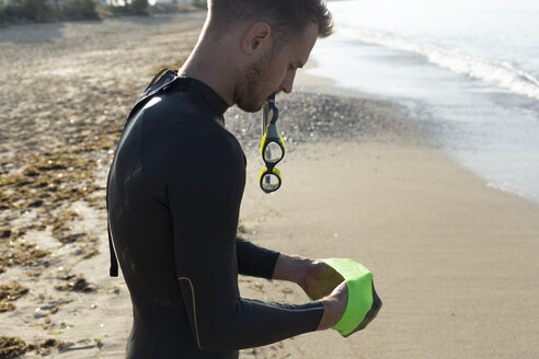 Triathlete putting on swimming goggles, getting ready for an ocean swim - JPTF00114