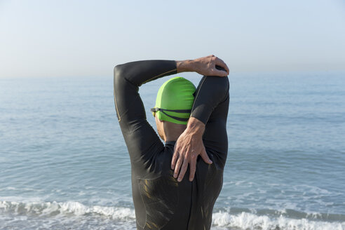 Triathlete preparing to swim, stretching arms and shoulders - JPTF00117