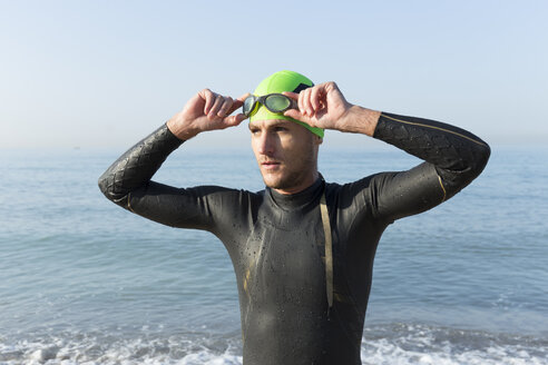 Triathlete preparing to swim, putting on swimming cap and goggles - JPTF00120