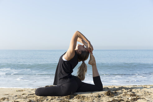 Young woman practicing yoga on the beach, doing pigeon pose - JPTF00123