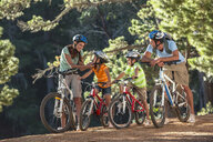 Family with mountain bikes in woods - JUIF01085