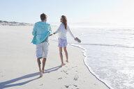 Couple walking on sunny beach - JUIF01109